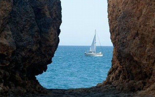 A sailboat near the algarve coast with rocks.