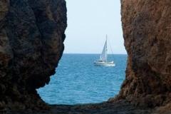 A sailboat near the algarve coast with rocks.